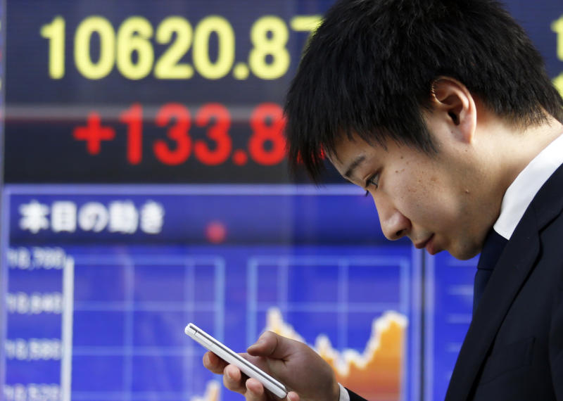 A man looks at his cellphone at an electronic stock board of a securities firm in Tokyo, Thursday, Jan. 24, 2013. Asian stock markets were mostly higher Thursday, supported by Congress averting a U.S. government default and a pickup in China's manufacturing in January.  (AP Photo/Koji Sasahara)
