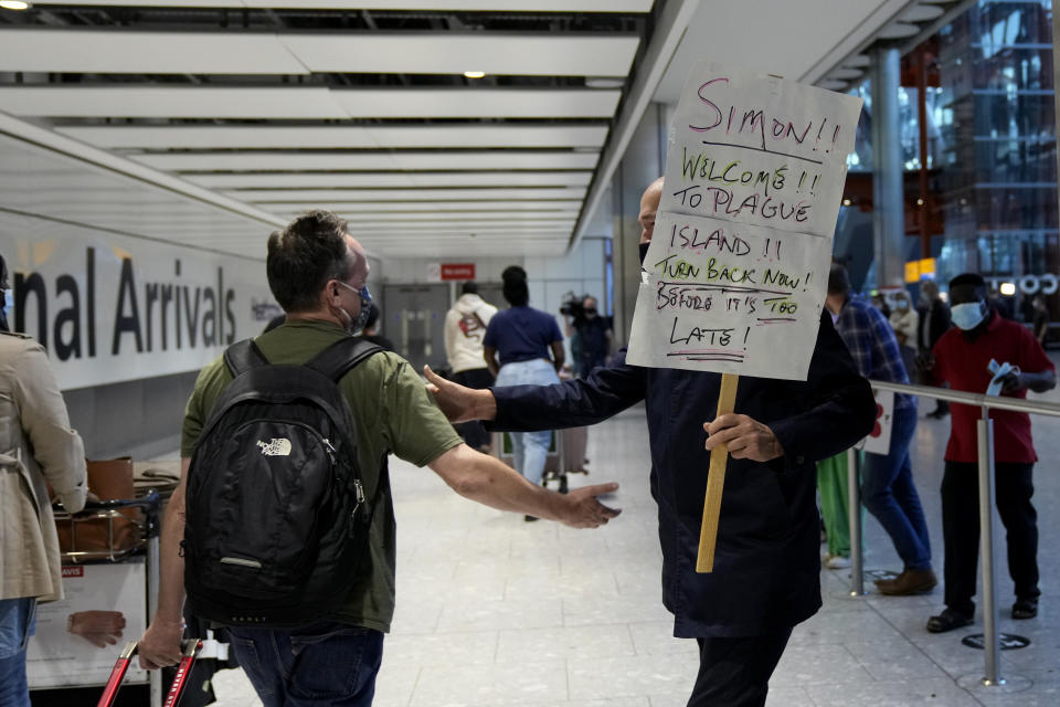 A man holds a sign as he greets his brother arriving on a flight at Terminal 5 of Heathrow Airport in London, Monday, Aug. 2, 2021. Travelers fully vaccinated against coronavirus from the United States and much of Europe were able to enter Britain without quarantining starting today, a move welcomed by Britain's ailing travel industry. (AP Photo/Matt Dunham)