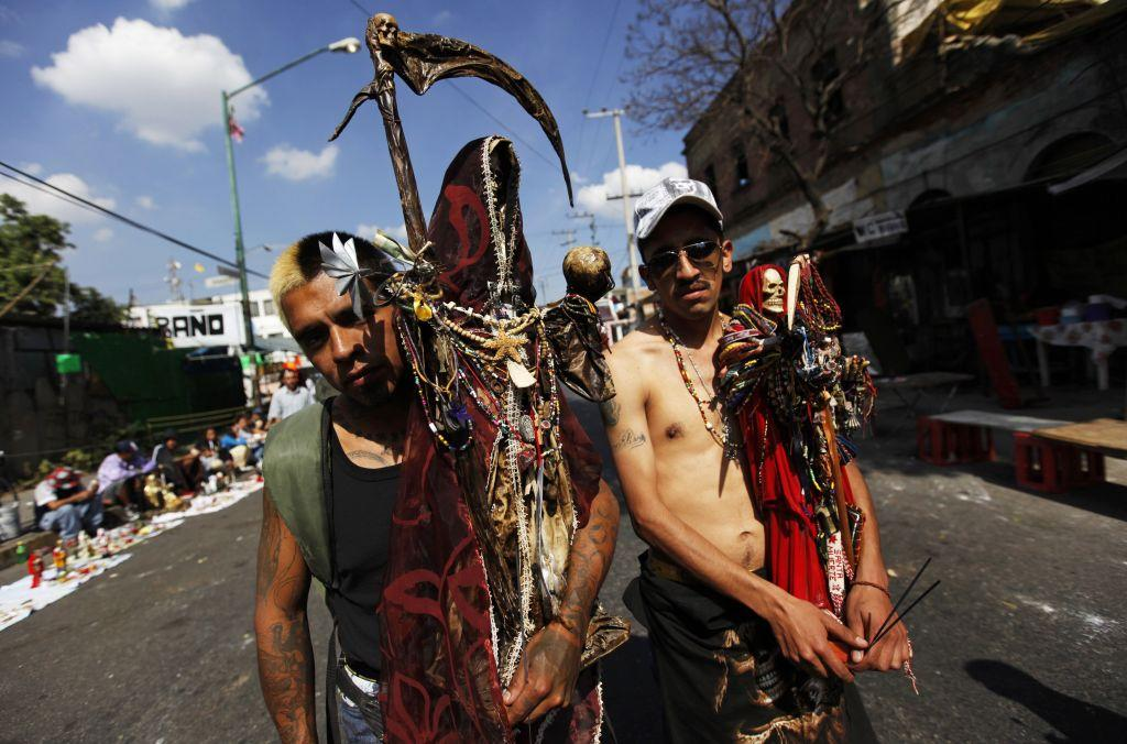 Followers of La Santa Muerte (The Saint of Death), a cult figure often depicted as a skeletal grim reaper, pose for a photograph at the saint's altar in Tepito, Mexico City January 1, 2013. Followers gather at the altar at the start of a new year, and subsequently on the first of each month, to leave offerings of apples, flowers, cigarettes, coloured candles and tequila to thank her for granted favours or to ask for new ones.