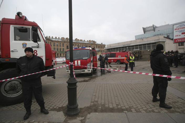 <p>Russian police and emergency service officers stand near fire trucks near the entrance of Sennaya Square subway station in St. Petersburg, Russia, Monday, April 3, 2017. (Evgenii Kurskov/AP) </p>