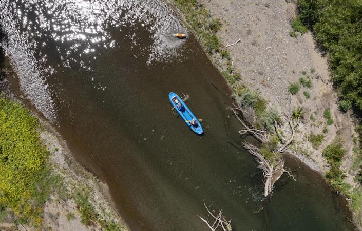 A canoe floats past an exposed gravel bar, right, on the Russian River in Healdsburg, Calif.