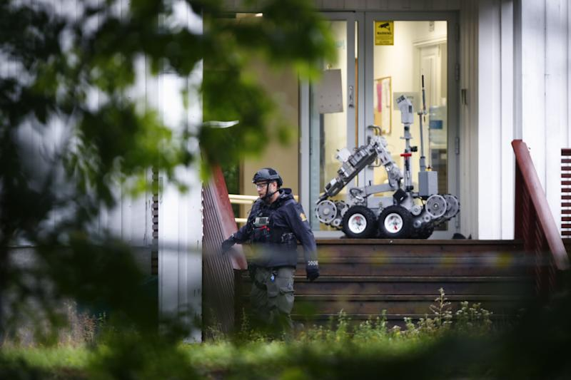 A Norwegian police expert walks past a robot in front of the al-Noor islamic center mosque where a gunman, armed with multiple weapons, went on a shooting spree in the town of Baerum, an Oslo suburb.