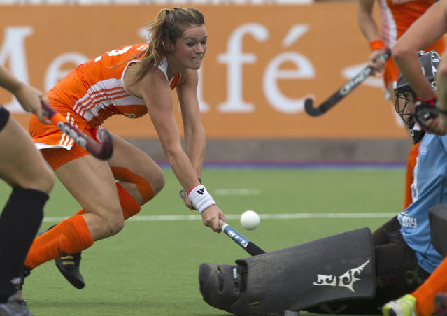 Netherlands' Lidewij Welten, left, battles for the ball with New Zealand goalkeeper Sally Rutherford in their Women's Champions Trophy quarterfinal field hockey match in Rosario, Argentina, Thursday Feb. 2, 2012. (AP Photo/Eduardo Di Baia)