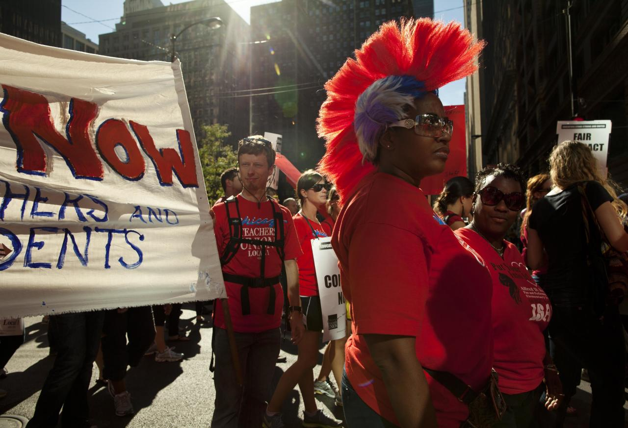 Michelle Harris, a teacher from Kohn School, sports a colourful wig as she marches with thousands of public school teachers for the second consecutive day on Tuesday, Sept. 11, 2012 in downtown Chicago. Teachers walked off the job Monday for the first time in 25 years over issues that include pay raises, classroom conditions, job security and teacher evaluations. (AP Photo/Sitthixay Ditthavong)