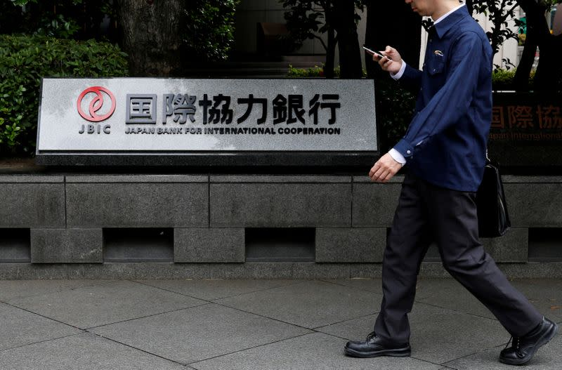 FILE PHOTO: Man walks past a sign of Japan Bank for International Cooperation (JBIC) at it's headquarters in Tokyo