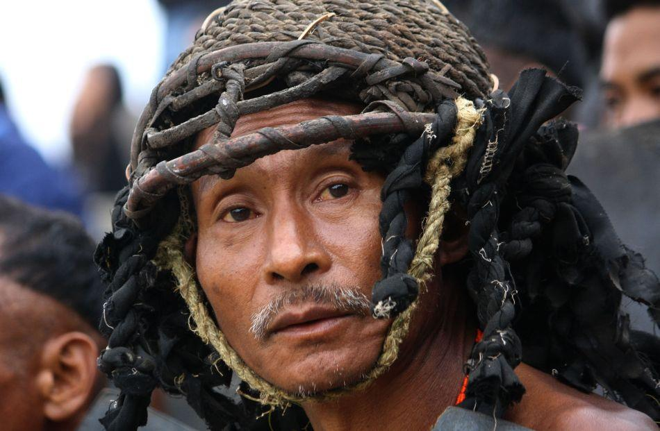 A Naga tribesman from Khiamniungan tribe with warrior headgear looks on as he waits to perform the 'war between neighbours' ritual.