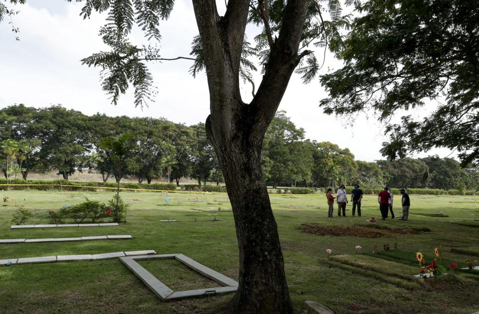 Forensic workers wait to begin an exhumation of what are believed to be the remains of Lt. Braulio Bethancourt, a victim of the 1989 U.S. invasion, at the Jardin de Paz cemetery in Panama City, Thursday, April 15, 2021. The prosecutor's office has begun an exhumation of human remains at the Panamanian cemetery in a renewed attempt to confirm the identities of the victims of the U.S. invasion. (AP Photo/Arnulfo Franco)