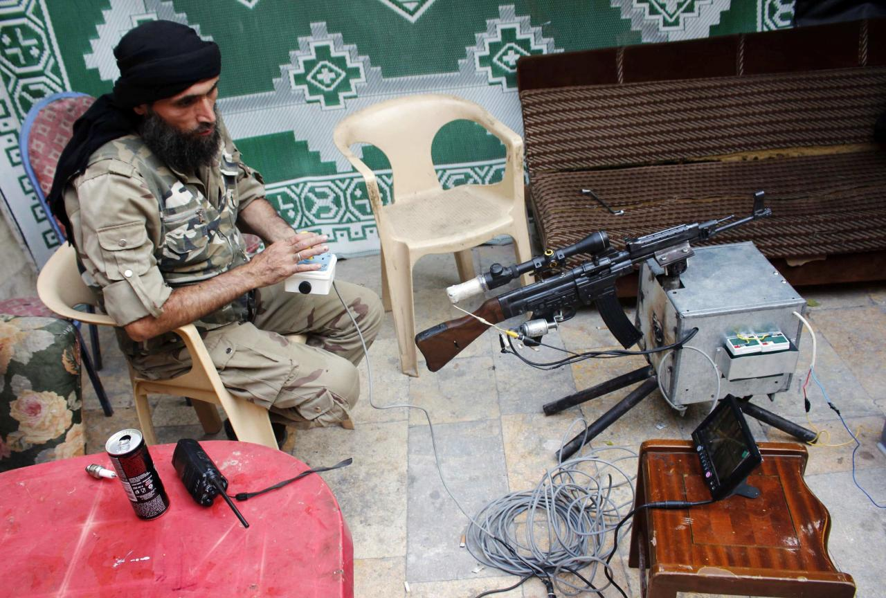 A Free Syrian Army fighter tests a remote-controlled weapon in the old city of Aleppo September 30, 2013. REUTERS/Molhem Barakat (SYRIA - Tags: POLITICS CIVIL UNREST CONFLICT MILITARY TPX IMAGES OF THE DAY)