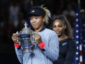 """FILE - Naomi Osaka, of Japan, holds the trophy after defeating Serena Williams, rear, in the women's final of the U.S. Open tennis tournament in New York, in this Saturday, Sept. 8, 2018, file photo. Naomi Osaka withdrew from the French Open on Monday, May 31, 2021, and wrote on Twitter that she would be taking a break from competition, a dramatic turn of events for a four-time Grand Slam champion who said she experiences """"huge waves of anxiety"""" before speaking to the media and revealed she has """"suffered long bouts of depression."""" (AP Photo/Adam Hunger, File)"""