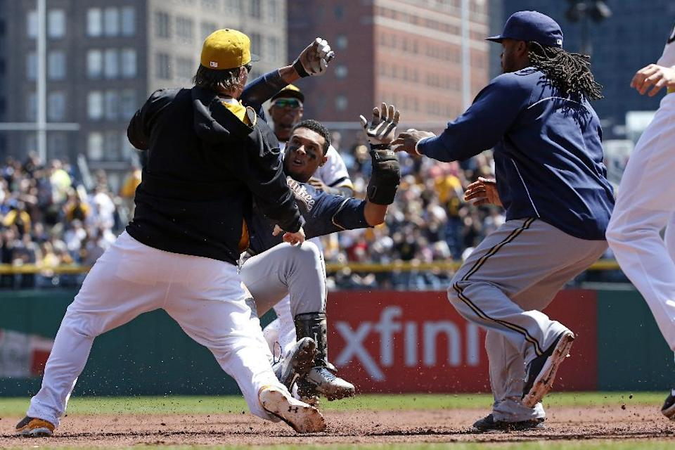 Pittsburgh Pirates' Travis Snider, left, takes down Milwaukee Brewers' Carlos Gomez as Brewers' Rickie Weeks, right, joins a skirmish between the two teams during the third inning of a baseball game in Pittsburgh, Sunday, April 20, 2014. Gomez and Snider were ejected from the game. (AP Photo/Gene J. Puskar)