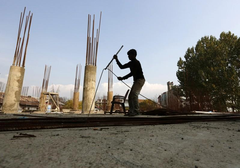 A migrant worker straightens an iron rod at the construction site of a parking lot in Srinagar