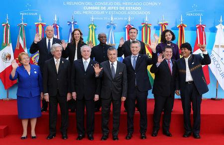 Chile's President Michelle Bachelet, Uruguay's President Tabare Vazquez, Brazil's President Michel Temer, Mendoza's Governor Alfredo Cornejo, Argentina's President Mauricio Macri, Paraguay's President Horacio Cartes and Bolivia's President Evo Morales (front row, L-R) alongside Peru's Ambassador to the Asia-Pacific Economic Cooperation (APEC) Luis Quesada, Colombia's Commerce, Industry and Tourism Minister Maria Claudia Lacouture, Guyana's Foreign Minister Carl Greenidge, Ecuador's head of the delegation Diego Rivadeneira Espinoza and Mexico's Ambassador in Argentina Mabel Gomez Oliver (L-R) pose for the official photo at the Mercosur trade bloc summit in Mendoza, Argentina July 21, 2017. REUTERS/Marcos Brindicci
