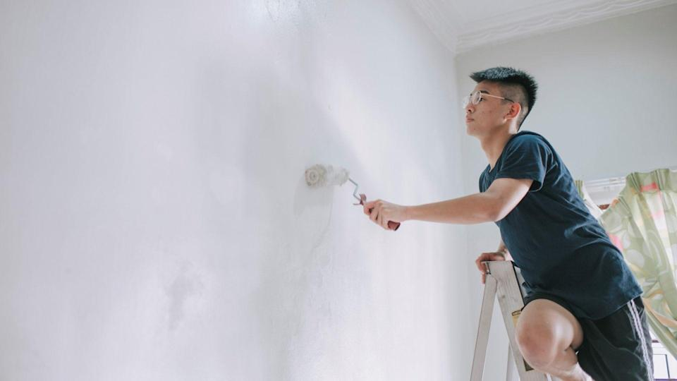 An asian chinese teenage boy painting his bedroom, apartment renovation during sunset.