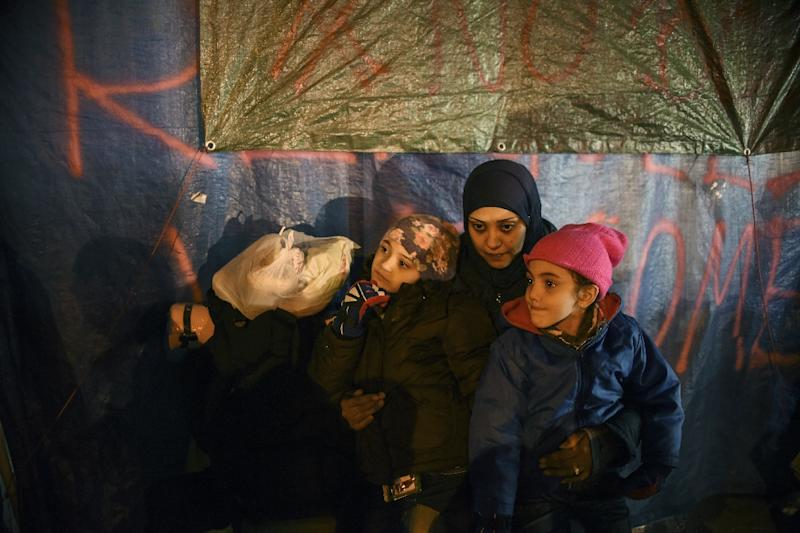 A woman waits with her children and other migrants and refugees to be registered at a center in Presevo, on October 25, 2015 (AFP Photo/Armend Nimani)