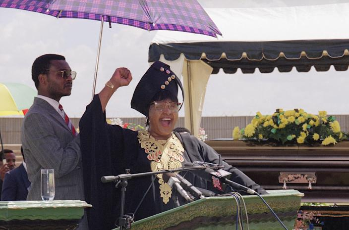 <p>Winnie Mandela, left, estranged wife of Nelson Mandela, salutes supporters while attending a funeral for a slain civic leader on, March 11, 1995 in Tembisa, South Africa. Embroiled in a corruption scandal that may cost her cabinet post, Winnie Mandela said she had not fought against apartheid to be treated as a criminal. Mrs. Mandela was attending the funeral of a squatter camp leader shot last week after voicing support for her in a television interview. (Photo: John Moore/AP) </p>