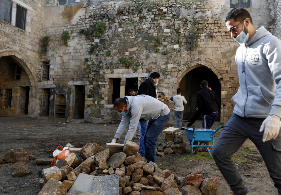 Architects and workers renovate the long-abandoned 200-year-old al-Kamalaia school, in the old quarter of Gaza City, Sunday, Dec. 20, 2020. Less than 200 of these old houses are still partly or entirely standing, according to officials and they are threatened by neglect, decaying and urban sprawl. (AP Photo/Adel Hana)
