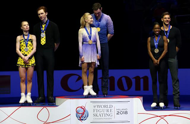 Figure Skating - World Figure Skating Championships - The Mediolanum Forum, Milan, Italy - March 22, 2018 Germany's Aljona Savchenko and Bruno Massot celebrate on the podium after winning the Pairs gold with Russia's Evgenia Tarasova and Vladimir Morozov who won silver and France's Vanessa James and Morgan Cipres who won bronze REUTERS/Alessandro Bianchi