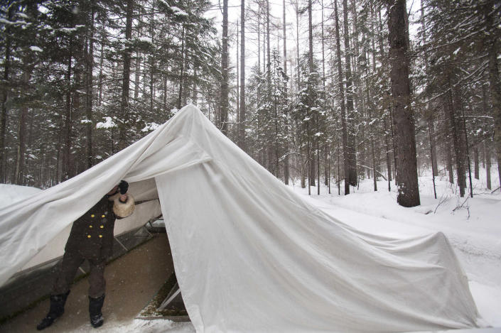 In this Wednesday, April 4, 2012 photo, a female North Korean soldier, working as a guide, opens a protective tent covering the remains of what is said to be a former camp site where the late North Korean leader Kim Il Sung spent the night while leading a battle against the Japanese at the foot of Mount Paektu, North Korea. (AP Photo/David Guttenfelder)