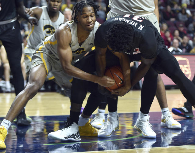 Iowa guard Bakari Evelyn (4) and San Diego State forward Nathan Mensah (31) fight for the ball during the first half of an NCAA college basketball game Friday, Nov. 29, 2019, in Las Vegas. (AP Photo/David Becker)