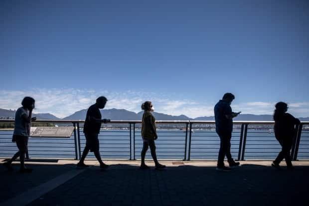 People wait in line outside Canada Place for their COVID-19 vaccination in Vancouver in June.  (Ben Nelms/CBC - image credit)