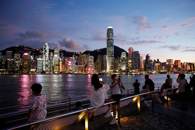 People enjoy the sunset view with a skyline of buildings during a meeting on national security legislation, in Hong Kong