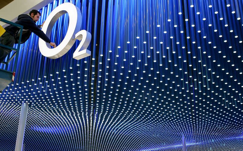 FILE PHOTO: A worker makes final touches on the logo of Britain's O2 in preparation for the CeBIT computer fair