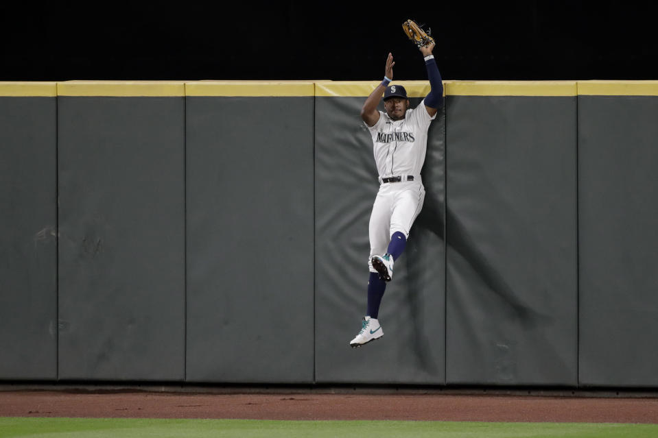 Seattle Mariners right fielder Kyle Lewis makes a leaping catch at the wall of a fly ball hit by Los Angeles Angels' Jason Castro during the seventh inning of a baseball game Tuesday, Aug. 4, 2020, in Seattle. (AP Photo/Ted S. Warren)