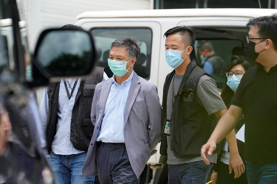 Police officers from the national security department escort Chief Operating Officer Chow Tat-kuen from the offices of Apple Daily and Next Media in Hong Kong, China June 17, 2021. REUTERS/Lam Yik