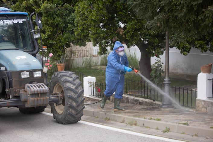 A volunteer disinfects the streets of Zahara de la Sierra in Spain during the coronavirus pandemic. (Getty Images)
