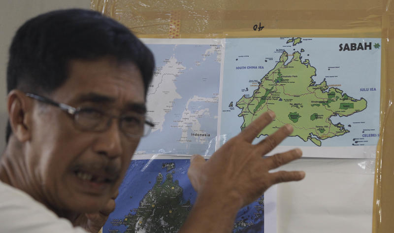 FILE PHOTO: Abraham Idjirani, spokesman for the Sultanate of Sulu, points at a map of Borneo's eastern Sabah state as he talks to reporters in suburban Taguig City, Philippines on Tuesday March 5, 2013. (AP Photo/Aaron Favila)