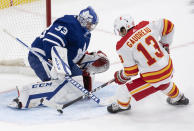 Calgary Flames' Johnny Gaudreau (13) scores the game winning goal on Toronto Maple Leafs goaltender David Rittich (33) during overtime in an NHL hockey game Tuesday, April 13, 2021 in Toronto. (Frank Gunn/Canadian Press via AP)