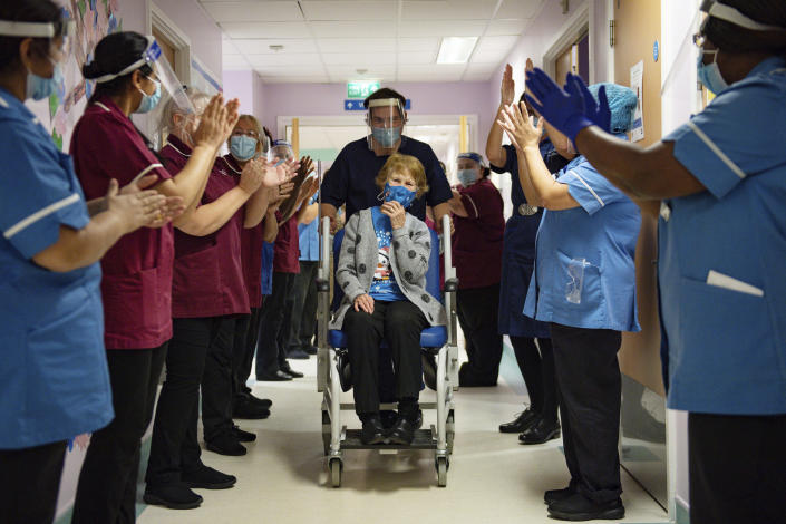 Margaret Keenan, 90, is applauded by staff as she returns to her ward after becoming the first patient in the UK to receive the Pfizer-BioNTech COVID-19 vaccine, at University Hospital, Coventry, England, Tuesday Dec. 8, 2020. The United Kingdom, one of the countries hardest hit by the coronavirus, is beginning its vaccination campaign, a key step toward eventually ending the pandemic. (Jacob King/Pool via AP)
