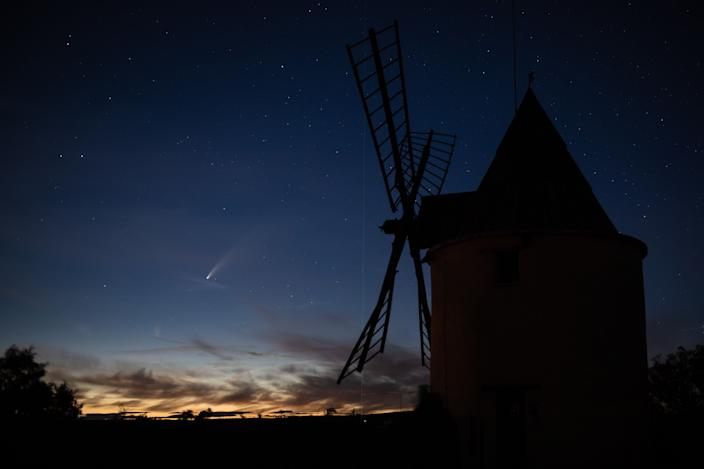A picture taken on July 15, 2020, shows Comet Neowise and the green laser beam used by the Haute-Provence Observatory to point celestial objects for studies and researches, with an old windmill in the foreground in Saint-Michel-L'Observatoire, southern France.