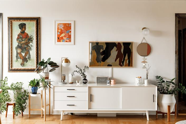"""<div class=""""caption""""> """"Artwork"""" above the credenza includes a <a href=""""https://fave.co/3aQDItG"""" rel=""""nofollow noopener"""" target=""""_blank"""" data-ylk=""""slk:Samsung TV"""" class=""""link rapid-noclick-resp"""">Samsung TV</a> in a wooden frame. """"I change the print out weekly,"""" the actress says. </div>"""