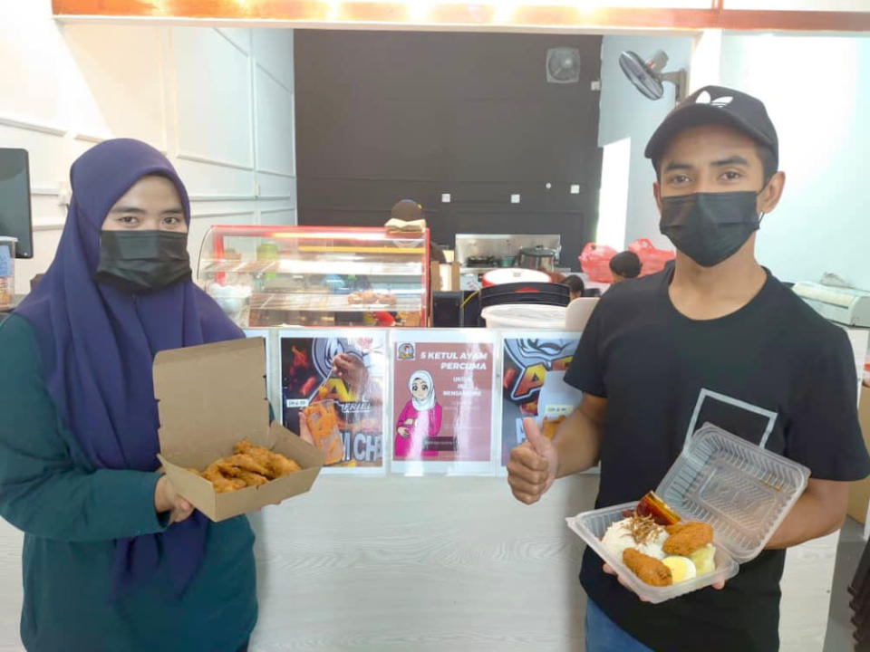 Kafe Ateyh Fried Chicken outlet owners Siti Nazirah Norzri (left) and her husband Mohammad Atif Wan Kamal showing the fried chicken and fried chicken nasi lemak meals in their shop. — Picture by Ben Tan