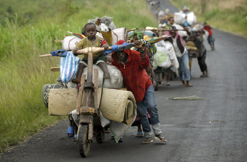 Congolese flee the eastern Congolese town of Sake, 27-kilometers west of Goma, Friday Nov. 23 2012. Thousands fled the M23 controlled town as platoons of rebels were making their way across the hills from Sake to the next major town of Minova, where the Congolese army was believed to be regrouping. The militants seeking to overthrow the government vowed to push forward despite mounting international pressure. (AP Photo/Jerome Delay)