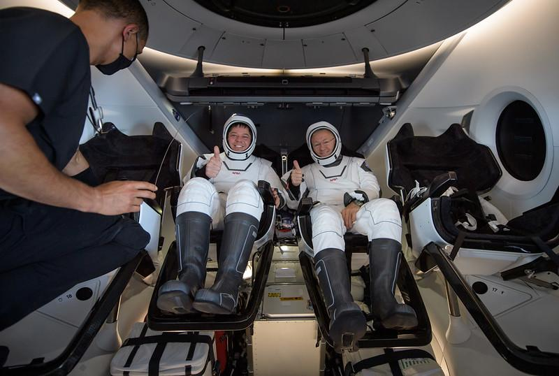 NASA astronauts BoB Behnken (left) and Doug Hurley are seen inside the SpaceX Crew Dragon Endeavour spacecraft onboard the GO Navigator recovery ship shortly after having landed in the Gulf of Mexico off the coast of Pensacola, Florida on Aug. 2, 2020.