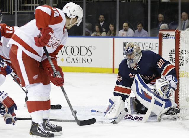 New York Rangers goalie Henrik Lundqvist (30), of Sweden, deflects a shot on the goal by Detroit Red Wings' Gustav Nyquist (14) during the first period of an NHL hockey game Thursday, Jan. 16, 2014, in New York. (AP Photo/Frank Franklin II)