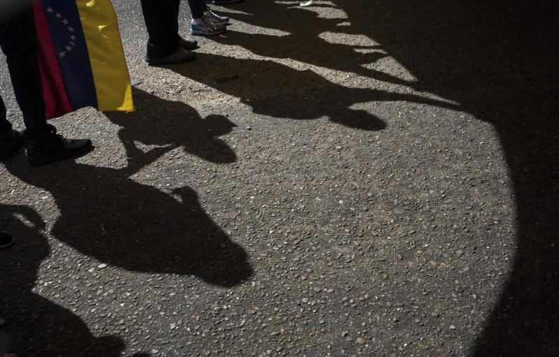 In this Nov. 16, 2019 photo, shadows of anti-government protestors are cast on the asphalt during a demonstration in Maracaibo, Venezuela. Opposition leader Juan Guaido, who seeks to oust President Nicolas Maduro, has urged Venezuelans to take to the streets, trying to reignite a movement started early this year. However, few in Maracaibo have responded, despite it being a city hard hit by crisis. (AP Photo/Rodrigo Abd)