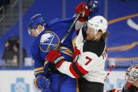 Buffalo Sabres forward Curtis Lazar (27) is checked by New Jersey Devils defenseman Matt Tennyson (7) during the second period of an NHL hockey game, Sunday, Jan. 31, 2021, in Buffalo, N.Y. (AP Photo/Jeffrey T. Barnes)