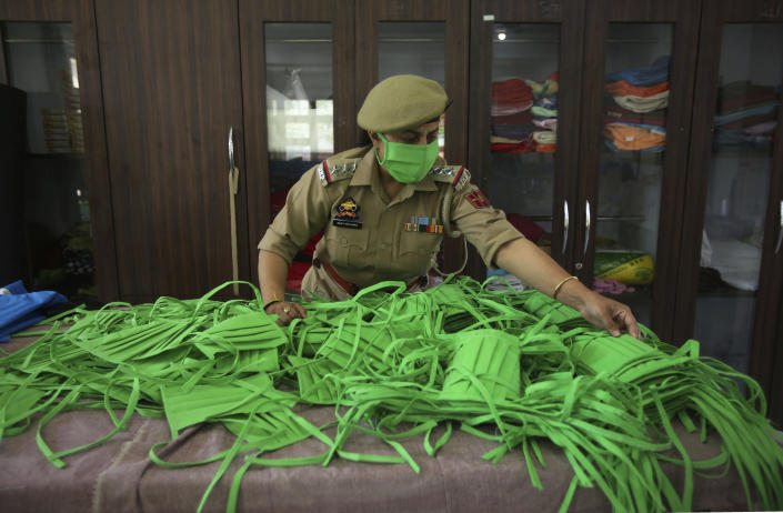 An officer checks the quality as Jammu and Kashmir police personnel make face masks and personal protective gear amid COVID-19 outbreak in Jammu, India, Wednesday, April 8, 2020. The new coronavirus causes mild or moderate symptoms for most people, but for some, especially older adults and people with existing health problems, it can cause more severe illness or death. (AP Photo/ Channi Anand)