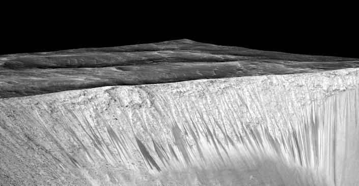 Narrow streaks on the slopes of Garni Crater are inferred to be formed by seasonal flow of water on surface of present-day Mars. (NASA)