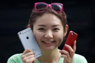 A woman holds a mock iPhone 6 plus (L) and an iPhone 5s as she waits in a line, ahead of the September 19 release of iPhone 6 and iPhone 6 Plus, in front of an Apple Store at Tokyo's Ginza shopping district September 10, 2014. REUTERS/Yuya Shino