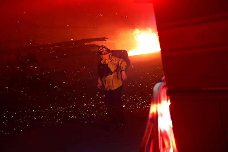 A firefighter gestures and hurries a man to direct a fire engine into position during the wind-driven Kincade Fire in Windsor, California, Oct. 27, 2019. (Photo: Stephen Lam/Reuters)