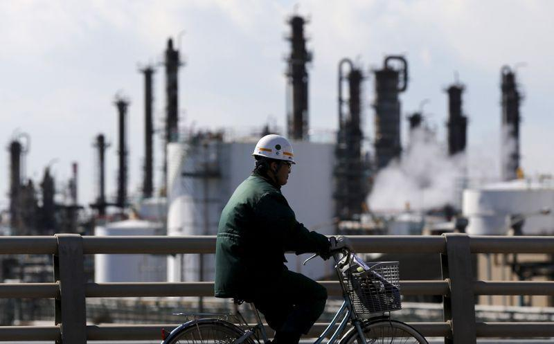 Worker cycles near a factory at the Keihin industrial zone in Kawasaki