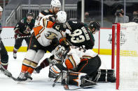 Anaheim Ducks goaltender Ryan Miller (30) makes a save under defenseman Jani Hakanpaa (28), defenseman Cam Fowler (4) and Arizona Coyotes right wing Conor Garland (83) during the second period of an NHL hockey game Wednesday, Feb. 24, 2021, in Glendale, Ariz. (AP Photo/Rick Scuteri)