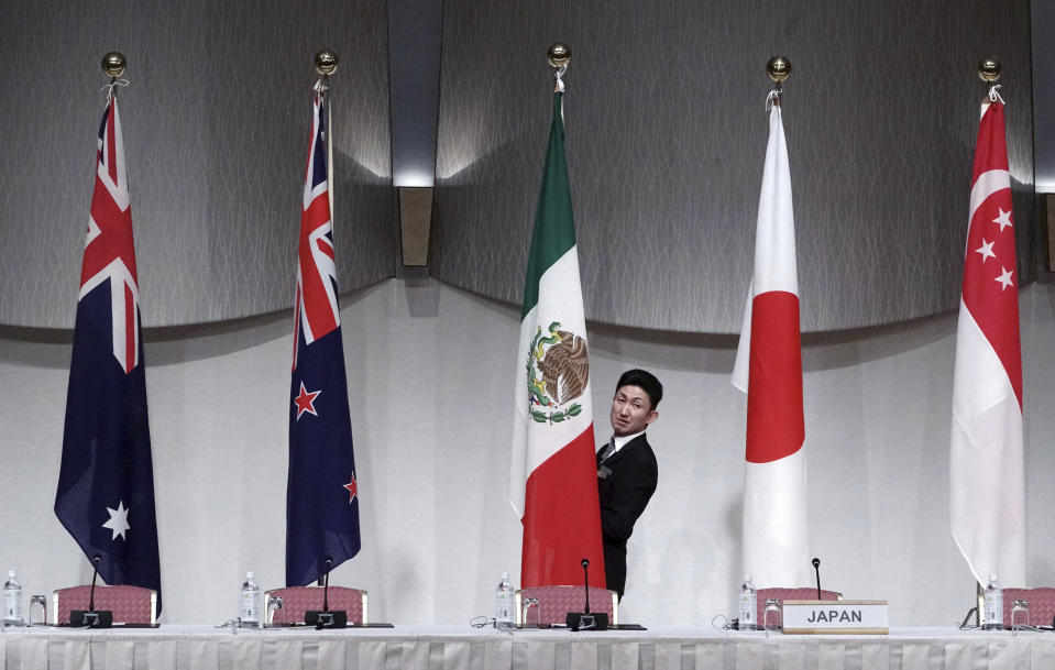 A staff adjusts the Mexican flag prior to a joint press conference of the Comprehensive and Progressive Trans-Pacific Partnership (CPTPP) in Tokyo, Japan, in 2019. Photo: AP Photo/Eugene Hoshiko.