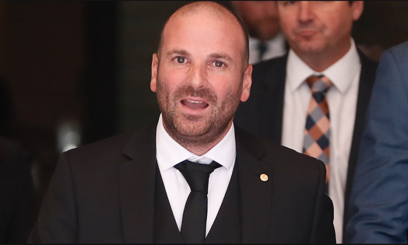 George Calombaris in a black suit and tie
