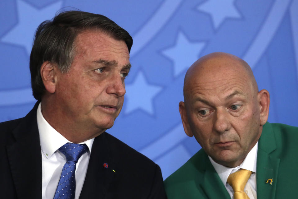 Brazil's President Jair Bolsonaro, left, talks with Brazilian billionaire businessman Luciano Hang during a ceremony to announce a  package of relief measures for the aviation industry, one of the most affected by the COVID-19 pandemic, at the Planalto Presidential Palace, in Brasilia, Brazil, Wednesday, Oct. 7, 2020. (AP Photo/Eraldo Peres)