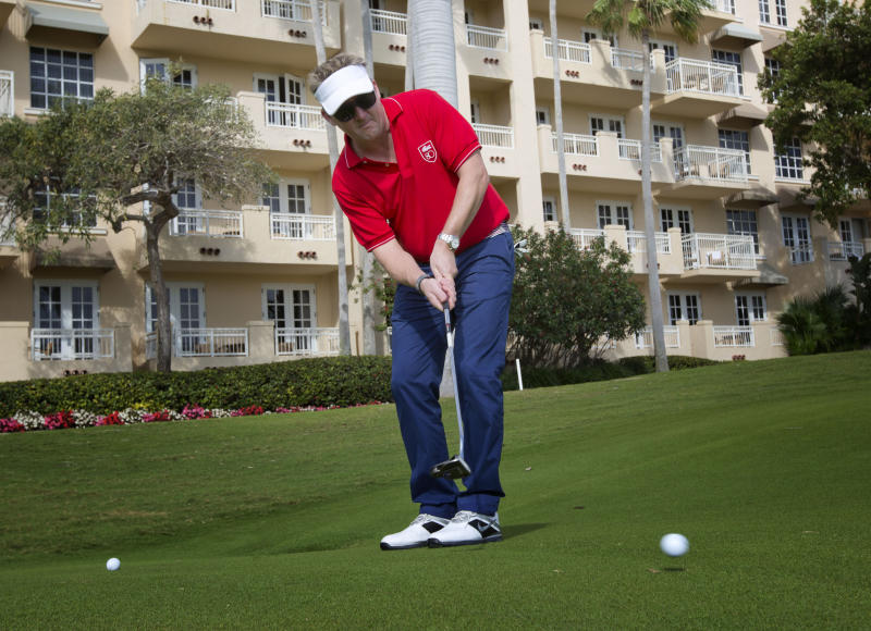 Chef Tim Love putts on a Miami Beach, Fla. golf course during a tournament Saturday, Feb. 23, 2013. Nearly a dozen A-list chefs took to the links early Saturday during the South Beach Wine and Food Festival for a battle of the chefs during a golf tournament.(AP Photo/J Pat Carter)
